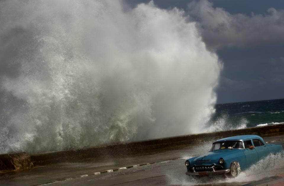 A driver maneuvers his classic American car along a wet road as a wave crashes against the Malecon in Havana, Cuba, Thursday, Oct. 25, 2012.  Hurricane Sandy blasted across eastern Cuba on Thursday as a potent Category 2 storm and headed for the Bahamas after causing at least two deaths in the Caribbean. (AP Photo/Ramon Espinosa)