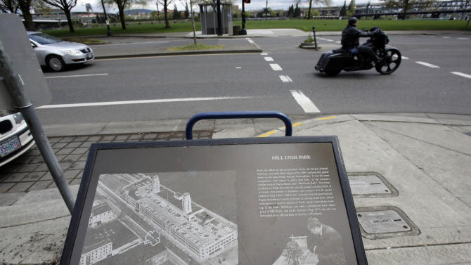 A plaque illustrates the history of Mill Ends Park, located just to the left of a passing motorcyclist,  in Portland, Ore., Thursday, April 11, 2013.  Tiny battle lines are being drawn in a whimsical British-American dispute over which country has the world's smallest park. Two feet in diameter, Portland's Mill Ends Park holds the title of world's smallest park in the Guinness Book of World Records. But a rival has emerged--Prince's Park, more than 5,000 miles away in the English town of Burntwood  which holds the record for smallest park in the United Kingdom.(AP Photo/Don Ryan)