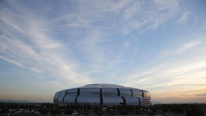In this Thursday, Dec. 11, 2014 photo, University of Phoenix Stadium, site of NFL Super Bowl XLIX football game, is seen here at sunset in Glendale, Ariz. The entire world will be watching Glendale on Sunday as it hosts the Super Bowl and the legions of fans who are shelling out big bucks to see the big game