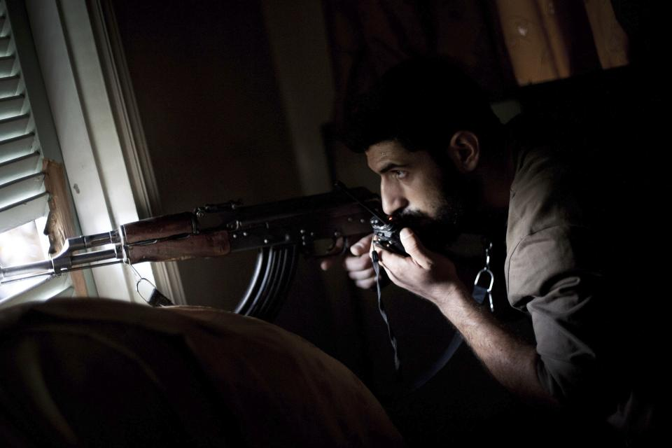 A Free Syrian Army fighter gives the Syrian Army positions to his comrades by radio in the Izaa district in Aleppo, Syria, Tuesday, Sept. 11, 2012. (AP Photo/Manu Brabo)