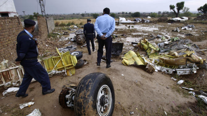 Pakistani police officers examine the site where a Bhoja Air Boeing 737 passenger plane crashed on Friday, killing all 127 people on board, on the outskirts of Islamabad, Pakistan, Sunday, April 22, 2012. Pakistan barred the head of the airline whose jet crashed near the capital from leaving the country, vowing to investigate the tragedy that revived fears about the safety of aviation in the country saddled by massive economic problems. (AP Photo/Muhammed Muheisen)
