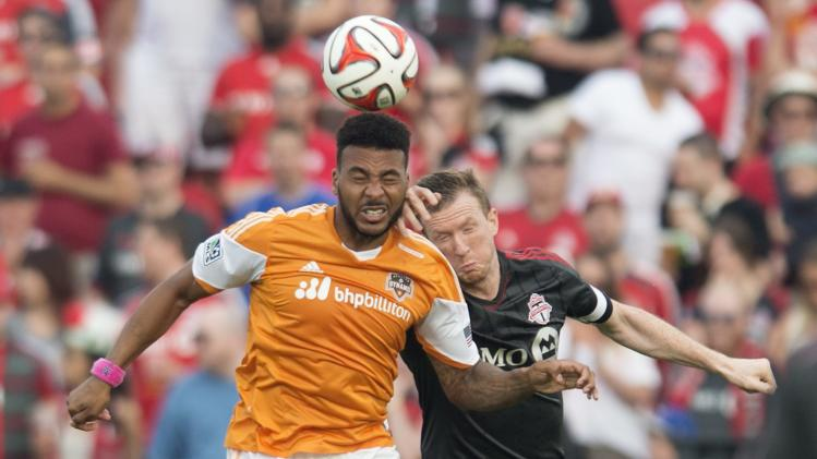 Houston Dynamo's Giles Barnes, left, and Toronto FC's Steven Caldwell battle for the ball during the first half of MLS soccer action in Toronto on Saturday, July 12, 2014. (AP Photo/The Canadian Press, Darren Calabrese)