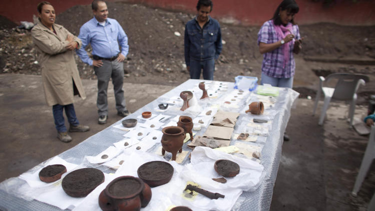 Archeologists stand next to a table displaying objects unearthed from a recently discovered archeological site in Mexico City, Friday, July 13, 2012. According to Mexico's National Institute of Anthropology and History, INAH, the site is about 700 years old and is a neighborhood of Tepaneca merchants. (AP Photo/Alexandre Meneghini)