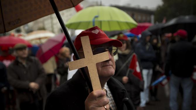 A demonstrator holds a cross during a demonstration against abortion in Madrid, Spain, Sunday, Oct. 17, 2013. (AP Photo/Daniel Ochoa de Olza)