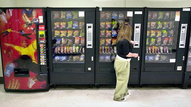 In this May 3, 2006 photo, a student purchases a brown sugar Pop-Tart from a vending machine in the hallway outside the school cafeteria, in Wichita, Kan. According to the first large study of states' laws governing the sale of junk food and drinks in U.S. public schools, these regulations may help curb childhood obesity. (AP Photo/The Wichita Eagle, Mike Hutmacher)