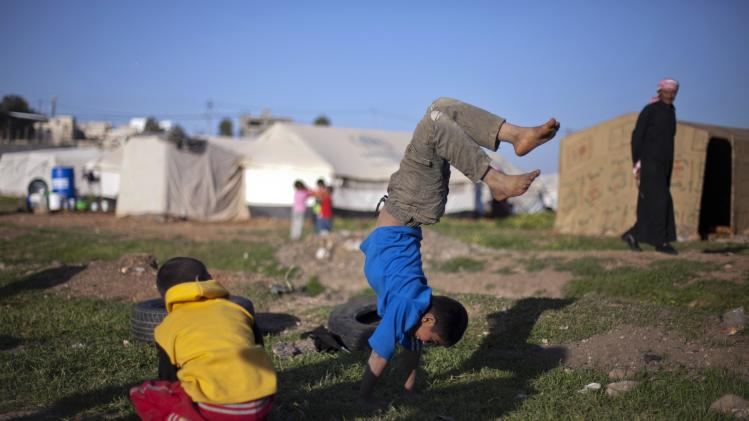 In this Friday, April 4, 2014 photo, Syrian boys play in an unofficial refugee camp on the outskirts of Amman, Jordan. Some residents, frustrated with Zaatari, the region's largest camp for Syrian refugees, set up new, informal camps on open lands, to escape tensions and get closer to possible job opportunities.(AP Photo/Khalil Hamra)