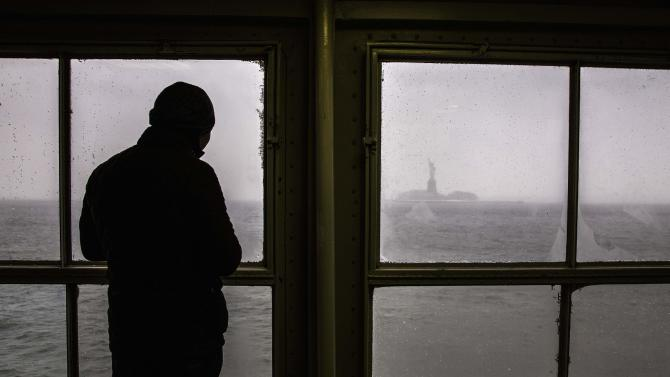 The Statue of Liberty is seen in the background as a man commutes on the Staten Island Ferry through New York Harbor