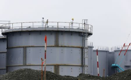 Workers wearing radiation protective gear stand on a water tank storing radiation contaminated water at TEPCO's tsunami-crippled Fukushima Daiichi nuclear power plant in Fukushima prefecture