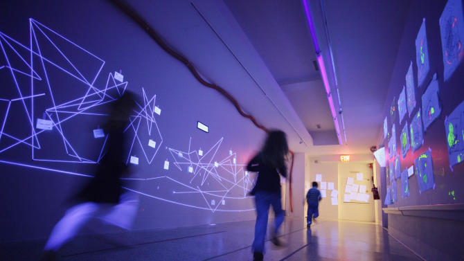In this March 31, 2011 photo, children run along a hallway illuminated by ultraviolet lamps at the Blue School in New York. The private preschool and elementary school was founded by original members of the Blue Man Group so they could send their own children to a school that was creative enough for them.  (AP Photo/Mark Lennihan)