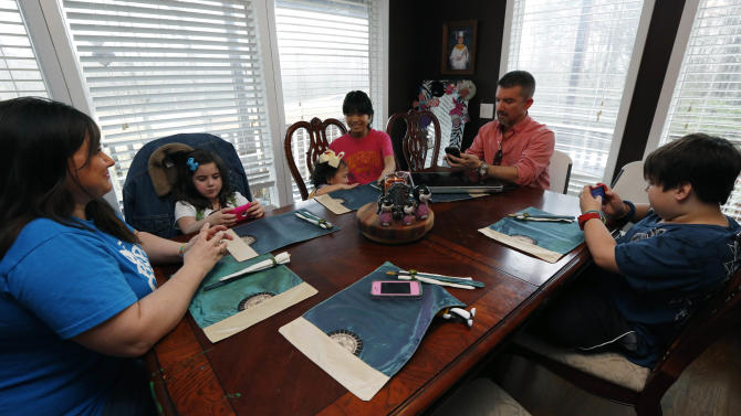 """In this April 4, 2013 photograph, Phillip Smith, right, and wife Niki, left,  are using Google Translate on their iPhones to """"speak"""" with their new daughter, 14-year-old Guan Ya, third from right, in their Rienzi, Miss., home. The Smiths and their three other children, Colton, 10, right, GiGi, 3, third from left, and Macy Jade, 7, second from left,  are using the program to communicate almost exclusively with Guan Ya, who is deaf. The family uses iPhones, iPods and a laptop, all loaded with the program to write in English that translates to Chinese and Guan Ya responds with Chinese to English. (AP Photo/Rogelio V. Solis)"""