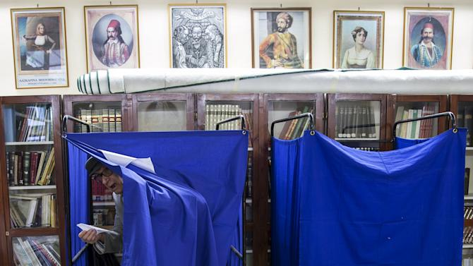 A man leaves polling booth to cast ballot during a referendum vote in Athens