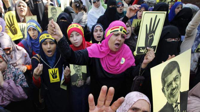 Supporters of Egypt's ousted President Mohammed Morsi raise his posters and their hands with four raised fingers, which has become a symbol of the Rabaah al-Adawiya mosque, where Morsi supporters had held a sit-in for weeks that was violently dispersed in August, during a protest in Cairo, Egypt, Friday, Nov. 22, 2013. (AP Photo/Amr Nabil)