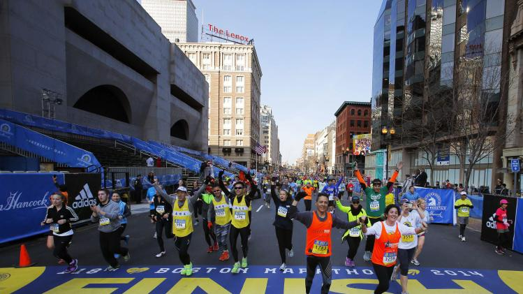 Runners cross over the Boston Marathon finish line while running the Boston Athletic Association's 5K race in Boston