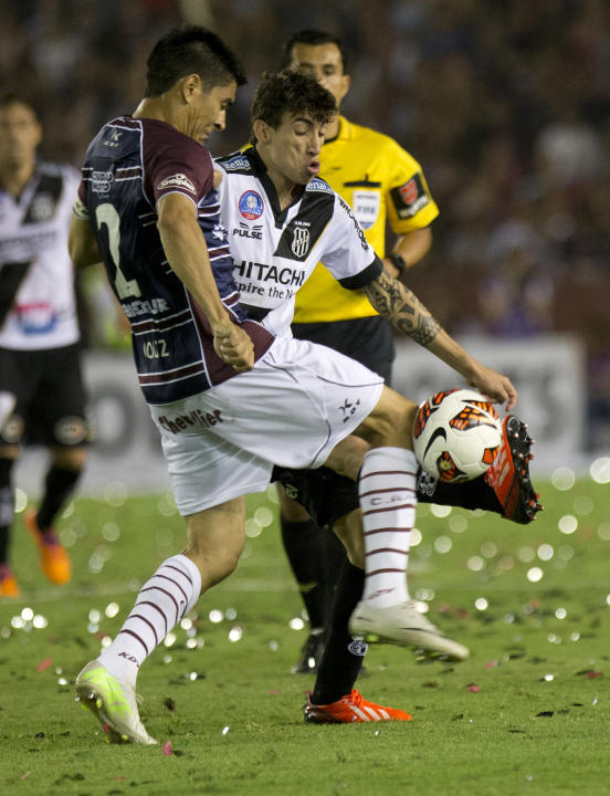 Brazil's Ponte Preta's Rildo, right, vies for the ball with Paolo Goltz of Argentina's Lanus during the Copa Sudamericana final soccer match in Buenos Aires, Argentina, Wednesday, Dec. 11,