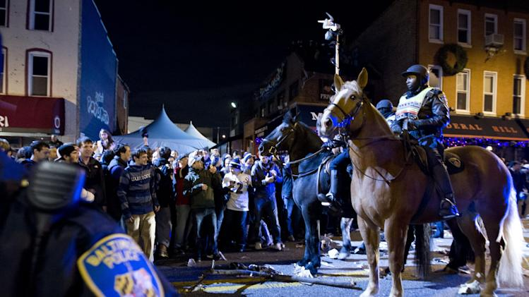 Police officers push back Baltimore Ravens fans who celebrate in the streets in downtown Baltimore after their team won the NFL football Super Bowl in a game against the San Francisco 49ers, Sunday, Feb. 3, 2013. (AP Photo/Jose Luis Magana)