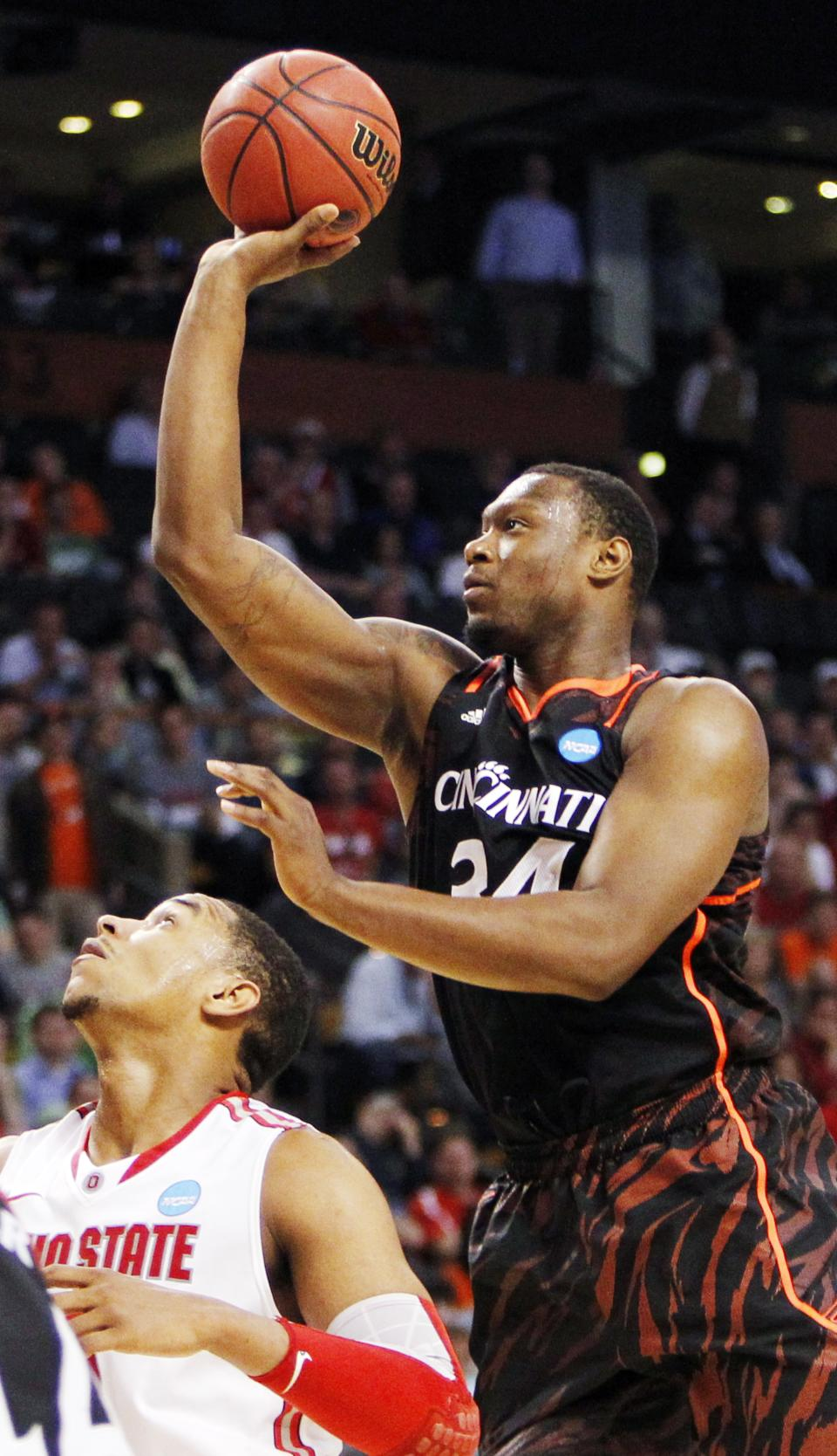 Cincinnati forward Yancy Gates (34) shoots over Ohio State forward Jared Sullinger, below, in the second half of an East Regional semifinal game in the NCAA men's college basketball tournament, Thursday, March 22, 2012, in Boston. (AP Photo/Michael Dwyer)