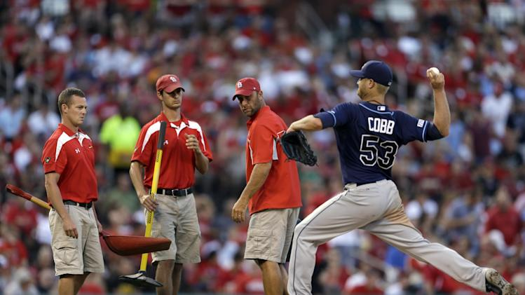 Members of the Busch Stadium grounds crew makes repairs to the mound as Tampa Bay Rays starting pitcher Alex Cobb prepares to throw during the fourth inning of a baseball game against the St. Louis Cardinals Wednesday, July 23, 2014, in St. Louis. (AP Photo/Jeff Roberson)