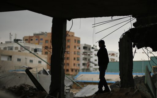 A Palestinian stands atop the rubble of a soccer stadium, which witnesses said was destroyed in an Israeli air strike during an eight-day conflict, in Gaza