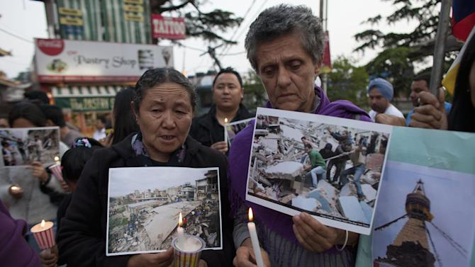Exile Tibetans and supporters hold photographs showing the devastation in Nepal during a candlelit vigil in solidarity with the people affected by the earthquake in Nepal and the border areas of India and China, in Dharmsala, India, Sunday, April 26, 2015.  Saturday's earthquake centered outside Kathmandu, the capital of Nepal, was the worst to hit the South Asian nation in over 80 years. It destroyed swaths of the oldest neighborhoods of Kathmandu, and was strong enough to be felt all across parts of India, Bangladesh, China's region of Tibet and Pakistan. (AP Photo/Ashwini Bhatia)