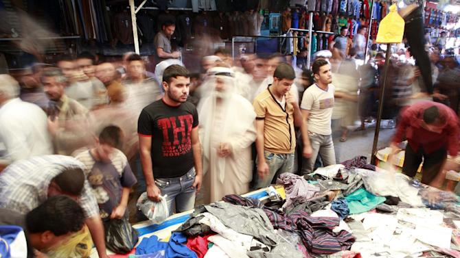 People shop for new clothes ahead of the upcoming Muslim holiday of Eid al-Adha in Baghdad, Iraq, Wednesday, Oct. 24, 2012. It is part of tradition to buy and wear new clothes during Eid al-Adha or the Feast of Sacrifice. (AP Photo/Hadi Mizban)