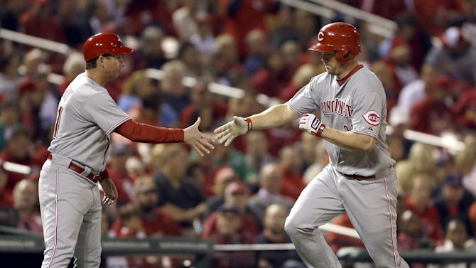 Cincinnati Reds' Scott Rolen, right, is congratulated by third base coach Mark Berry while rounding the bases after hitting a solo home run during the fourth inning of a baseball game against the St. Louis Cardinals, Tuesday, Oct. 2, 2012, in St. Louis. (AP Photo/Jeff Roberson)