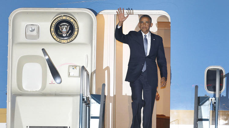 President Barack Obama waves as he walks down the stairs of Air Force One upon his arrival at San Francisco International Airport, Tuesday, July 22, 2014, in San Francisco. (AP Photo/Tony Avelar)