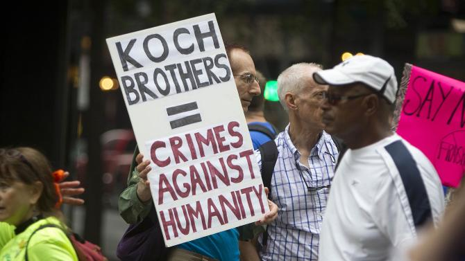 "A protester holds up a sign against the Koch Brothers at the ""People's Climate March"" down 6th Ave. in Manhattan, New York"