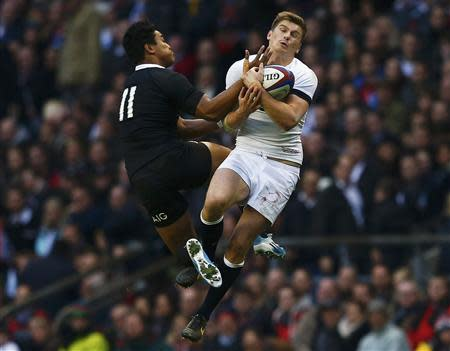 England's Farrell catches a high ball as he is challenged by New Zealand's Savea during international rugby union match at Twickenham in London
