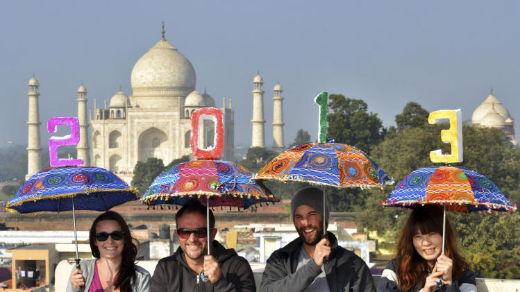 Tourists pose as they carry umbrellas with numbers to welcome the New Year 2013 on the terrace of a hotel in the backdrop of Taj Mahal in Agra, India, Monday, Dec. 31, 2012. (AP Photo/Pawan Sharma)
