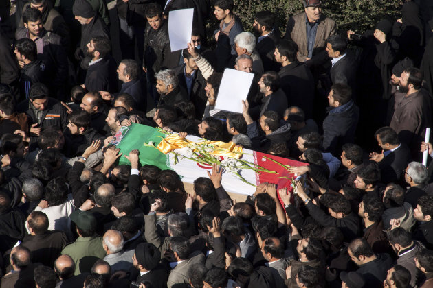 Iranian mourners carry the flag draped coffin of Gen. Hassan Shateri, during a funeral ceremony, in Tehran, Iran, Thursday, Feb. 14, 2013. Prominent Iranian politicians and clerics led mourners at a f