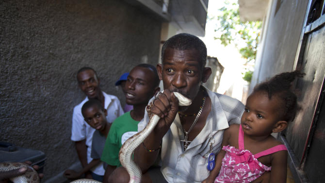 In this Jan. 27, 2013 photo, a man kisses a snake for good luck after paying snake handler Saintilus Resilus performing in the street during the pre-Lenten Carnival season in Petionville, Haiti. It's the serpents that help Resilus eat and pay rent, in addition to his work for a neighborhood herbologist. And it's the snakes for which he's most famous. (AP Photo/Dieu Nalio Chery)