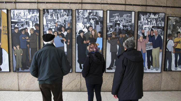Richard Bamforth, left, his wife Pat Bamforth, right, and their granddaughter, Pippa Adam, look at a mural depicting Maine's labor history on Monday, Jan. 14, 2013, in Augusta, Maine. The mural was put on  public display in the atrium leading to the Maine State Museum 22 months after Gov. Paul LePage ordered it removed from the Labor Department lobby. (AP Photo/Clarke Canfield)