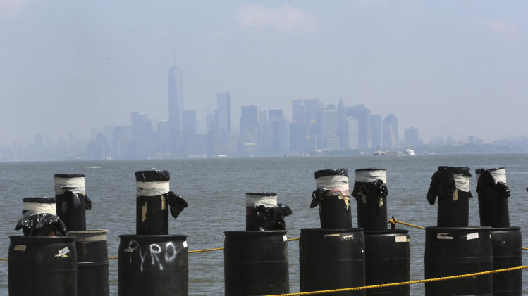 Mortars placed on a barge docked in the Staten Island borough of New York are in front of the hazy lower Manhattan skyline, Saturday, June 29, 2013. Forty thousand shells are being loaded onto four barges in preparation for the Macy's Fourth of July fireworks display. (AP Photo/Mary Altaffer)