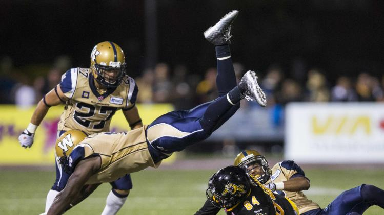 Tiger-Cats' Grant is tackled as Blue Bombers' Kuale goes flying over him during the second half of their CFL football game in Hamilton