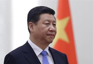 China's President Xi Jinping stands next to a Chinese national flag in Beijing