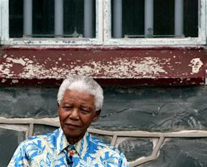 Nelson Mandela sits beneath the window of his prison cell on Robben Island