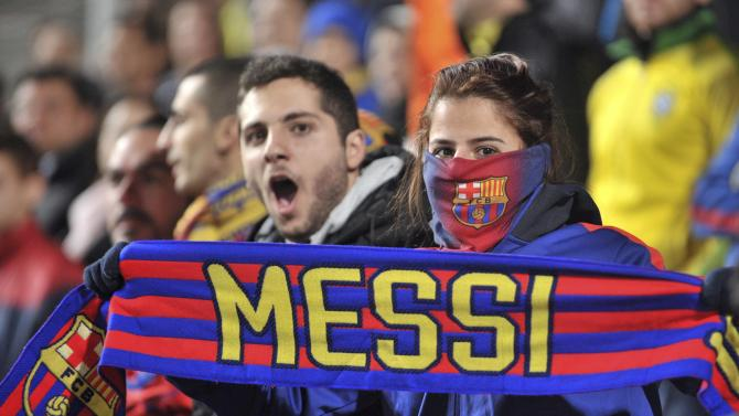 A Barcelona fan holds a scarf with Messi's name on it during the Champions League Group F soccer match between APOEL Nicosia and Barcelona in Nicosia