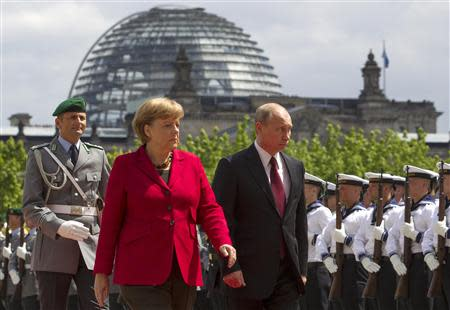 File photo of German Chancellor Merkel and Russian President Putin inspecting honour guards in Berlin