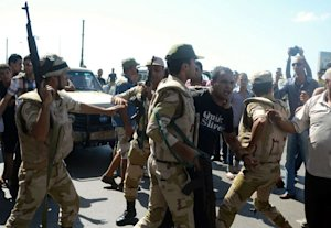 Security forces arrest an anti-government protester…