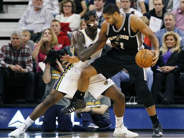 San Antonio Spurs' Tim Duncan, right, looks for an opening as Utah Jazz's Marvin Williams, left, defends in the second half of an NBA basketball game on Saturday, Dec. 14, 2013, in Salt Lake C