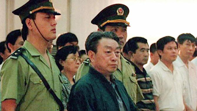 FILE - In this July 31, 1998 file photo released by China's Xinhua News Agency, former Beijing Mayor and Communist Party leader Chen Xitong, center, stands in Beijing's Municipal Higher Peoples Court. Chen, who backed the military crackdown on the Tiananmen Square democratic movement during his term but later expressed regret, died Sunday, June 2, 2013 at the age of 82, two days before the 24th anniversary of the bloody quelling of the student-led movement, according to media reports and a family friend. At the height of his career, Chen was one of China's most powerful men, but an anticorruption campaign brought about his spectacular downfall. (AP Photo/Xinhua, File) NO SALES