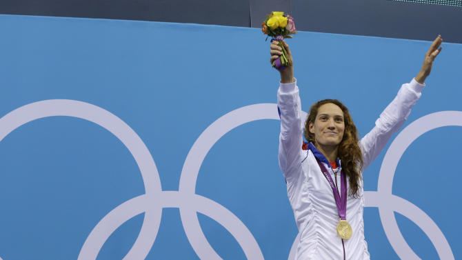 France's Camille Muffat celebrates with her gold medal for the women's 400-meter freestyle swimming final at the Aquatics Centre in the Olympic Park during the 2012 Summer Olympics in London, Sunday, July 29, 2012. (AP Photo/Michael Sohn)