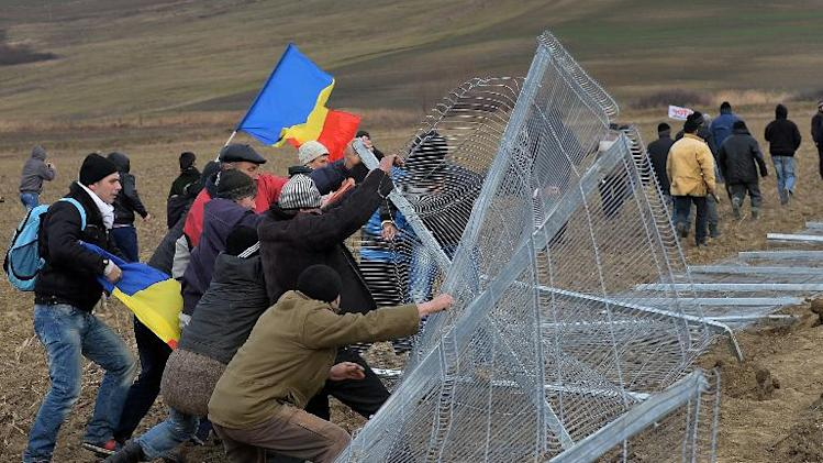 Romanian protesters break the fence of the exploring perimeter of US energy giant Chevron in Pungesti, Romania on December 7, 2013