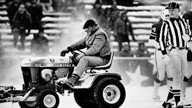 FILE - In this Dec. 13, 1982, file photo, Mark Henderson clears snow as referee Bob Frederic watches during the third quarter of an NFL football game between the New England Patriots and Miami Dolphins at Schaefer Stadium in Foxborough, Mass. (AP Photo/Mike Kullen, File)