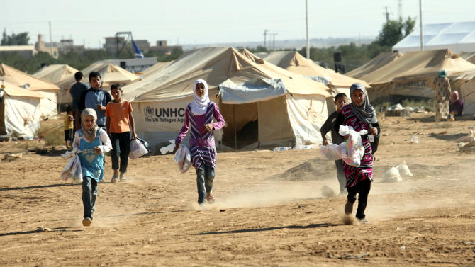Syrian refugee children run while carrying traditional gifts of toys and clothes they received from individual donors and international organizations on the first day the Muslim holiday of Eid al- Fitr at the Zaatari Refugee Camp in Mafraq, Jordan, Sunday, Aug. 19, 2012. Muslims around the world celebrate Eid al-Fitr, marking the end of Ramadan, the Muslim calendar's ninth and holiest month during which followers are required to abstain from food and drink from dawn to dusk. (AP Photo/Mohammad Hannon)