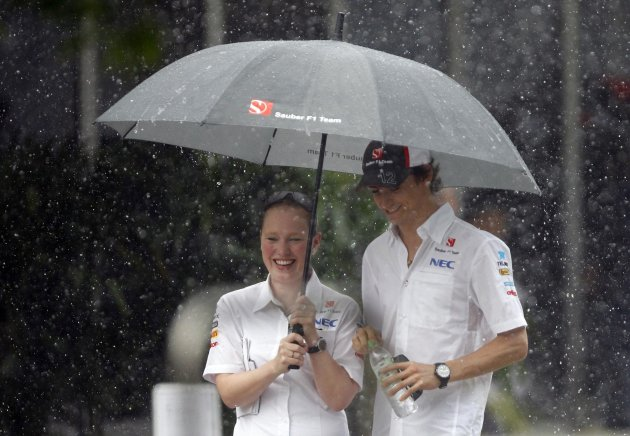 Sauber F1 driver Gutierrez of Mexico is sheltered from the rain by a team member as they walk in the paddock of Sepang International Circuit