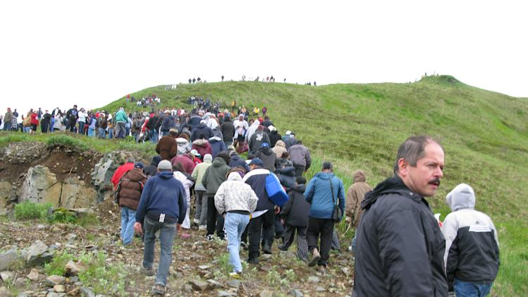 Fish processing workers and local residents head up the hill after a tsunami warning was issued Thursday night June 23, 2011 in Unalaska's Dutch Harbor, in Alaska's Aleutian Islands. The warning was triggered by an offshore earthquake. It was canceled after about half an hour. (AP Photo/Jim Paulin)
