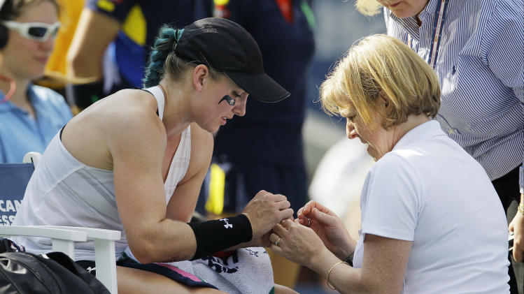 A trainer helps Bethanie Mattek-Sands during her match with Venus Williams in the first round of play at the 2012 US Open tennis tournament, Tuesday, Aug. 28, 2012, in New York. (AP Photo/Kathy Willens)