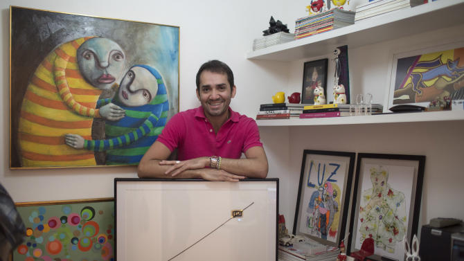 "In this Aug.  21, 2012 photo, Beto Silva, who works as a salesman at a luxury clothing store, poses for a photo with his art piece by artist Waltercio Caldas, titled ""Fim Fim,""' or ""End End,"" inside his apartment in Rio de Janeiro, Brazil. Like other thriving middle-class Brazilians, Silva has bought his way into the growing ranks of collectors who are helping to put Rio de Janeiro on the international art map.  (AP Photo/Felipe Dana)"
