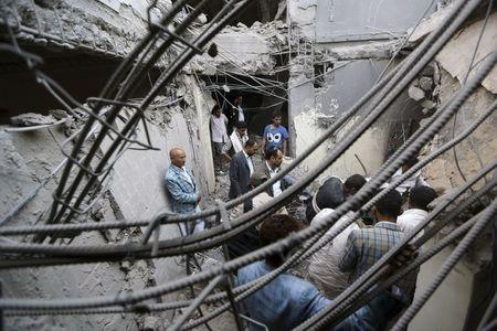 People search for survivors under the rubble of the collapsed house of Yemen's late prime minister Ghanim after it was hit by a Saudi-led air strike in Sanaa